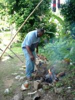 Jamaican man cooking over a wood fire
